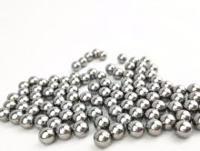 A large number of metal ball bearings sit on a white surface