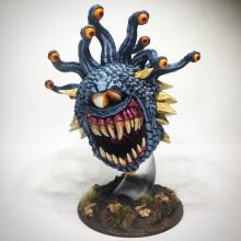 A blue beholder bears its many teeth.