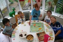 A group of young kids enjoying a game of monopoly and a few sweet snacks.