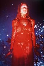 She stands in her prom dress covered in blood