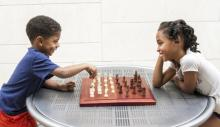 Two smiling siblings playing chess together.