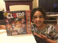 A sweet smiliing girl eager to play her new game, Cluedo Jr.