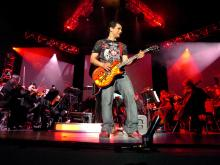 Rousing the crowd with an electrifying guitar solo (Photo by Melissa Estuesta, taken from http://videogameslive.com/gallery/v/flyers/)