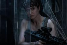 The main female character, known only as Daniels (Katherine Waterston) watches for xenomorphs with a very large assault rifle.
