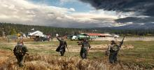 A group of 4 armed men approach a country town across a field.