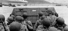 A group of soldiers look out over the battle on the beach that their transport boat is about to drop them off at.
