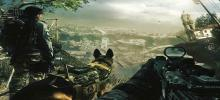 Two soldiers stand on a mountainside looking down over the city below them with their canine unit standing between them.