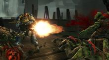 A Space Marine guns down advancing Orks with his heavy bolter