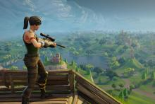 Player with a sniper rifle overlooks the vast landscape of Fortnite.