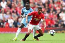 Marcus Rashford speeds past his opponent to get the ball