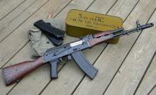 The rifle rests on top of a tin filled with 5.45x39 PS rounds.