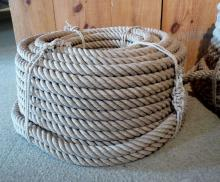 A hefty length of coiled rope sits against a wooden table