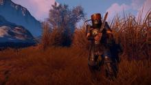 A heavily armored Rust player crouches near some tall grass.