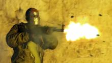 A fully geared player fires his gun in the dark.