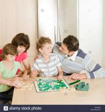 Two young kids playing scrabble with their parents.