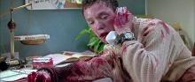 Stu crouches over the phone covered in blood