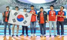 South Korea's team hoist their country's flag as they pose after their victory in the Overwatch cup