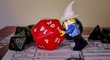 A Wizard miniature pushes a d20.